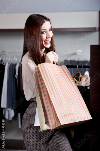 Woman carries paper bags after successful purchase