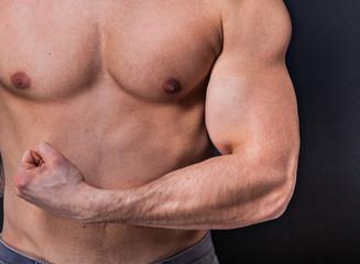 Sportlicher Mann spannt die Muskeln an