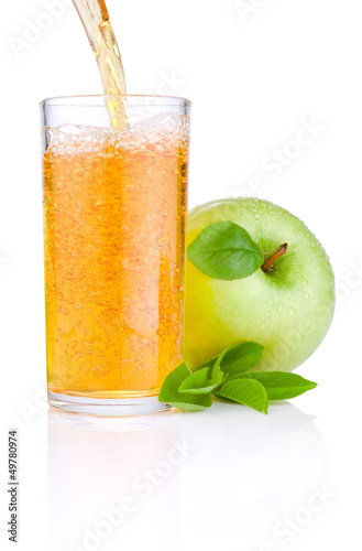 Pouring apple juice into a glass, green juicy apples with green