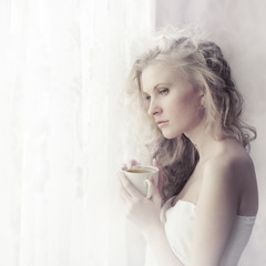 beautiful girl with a cup of coffee in the morning at the window