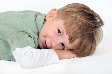 smiling boy lying on a white background