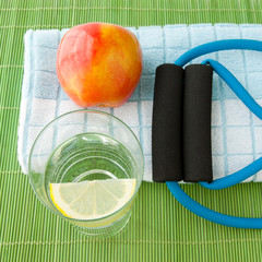 Healthy lifestyle concept - water, apple, expander and towel.