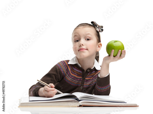 Schoolgirl with a green apple does her homework