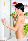 Woman eating near the opened refrigerator