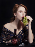 Portrait of beautiful rich women with grapes.