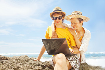 people with laptop on the beach