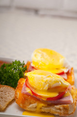 eggs benedict on bread with tomato and ham
