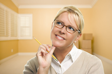Daydreaming Woman with Pencil in Empty Room and Boxes
