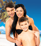 Happy family with child at tropical beach