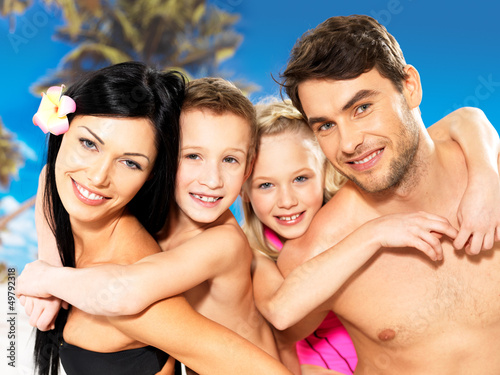 Happy family with two children at tropical beach