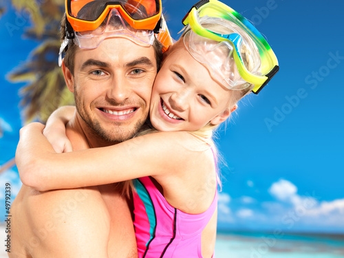 happy smiling father hugs daughter at tropical beach