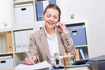 Frau im Büro telefoniert mit Smartphone