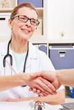 Doktor und Patient machen Handschlag
