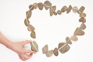 Hand legt Steine als Herz als Symbol für Liebe