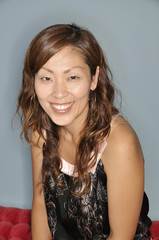 Head and shoulders of a smiling Asian woman