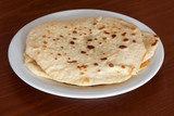 Stack of flour tortillas on plate