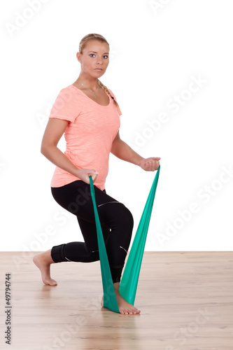 Athletic woman working out with a strap