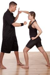 Woman and man practising kick boxing