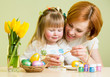 happy mother teaches daughter to paint easter eggs