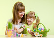 mother and child girl paint easter eggs over green