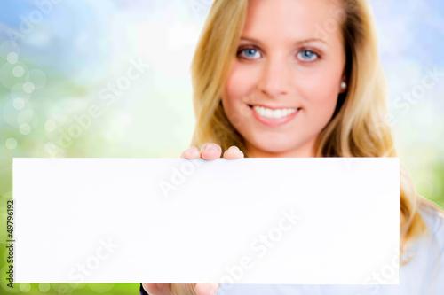 lächelnde junge frau zeigt hinweisschild