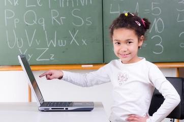 schülerin zeigt auf laptopbildschirm