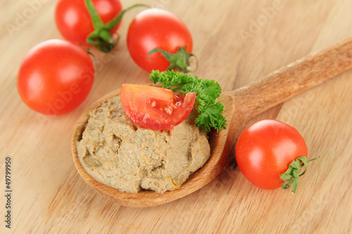 Fresh pate on wooden spoon, on wooden background