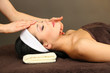 Beautiful young woman in spa salon taking head massage,