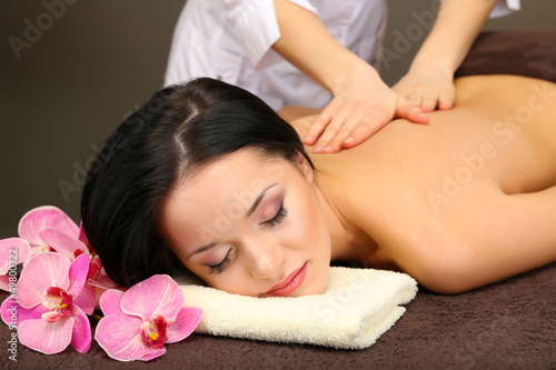 Beautiful young woman in spa salon getting massage with spa