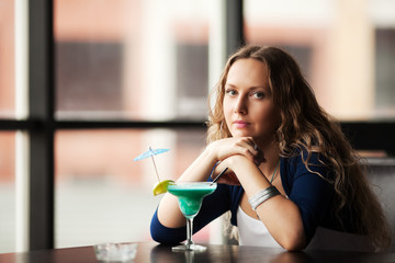 Sad young woman with cocktail at restaurant