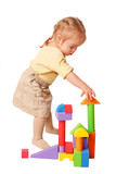 Baby girl building from toy blocks.