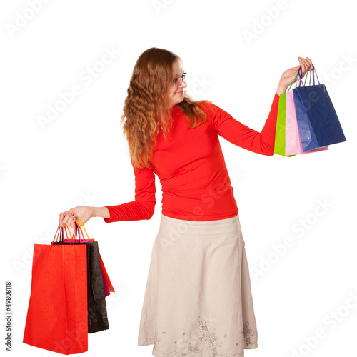 Shopping woman in glasses holding many shopping bags