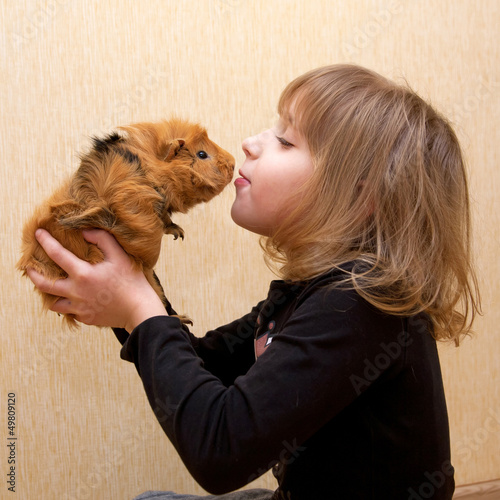 The little girl kissing the guinea pig.