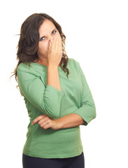 Attractive girl in a green shirt from the stench covers her nose