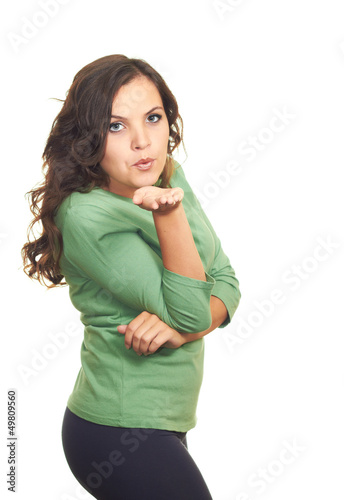 Attractive girl in a green shirt blowing a kiss at you.