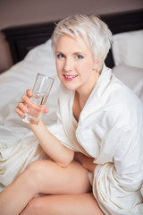 image of a woman on a hotel bed drinking water
