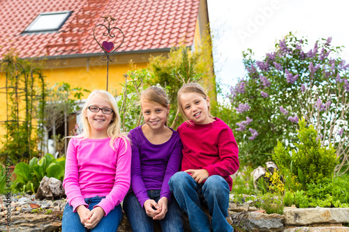 Laughing kids sit in front of the house in the garden