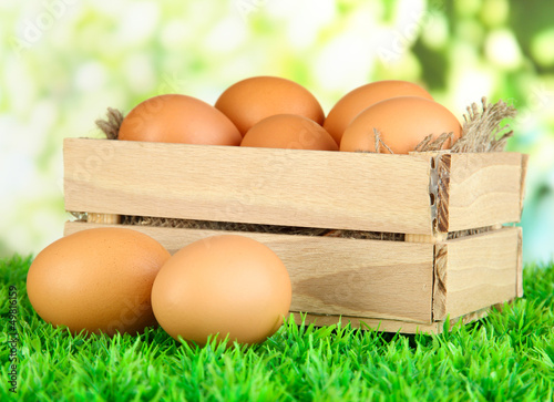 Many eggs in box on grass on bright background