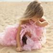 Beautiful little girl in a pink dress walking
