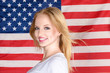 Young blonde girl posing against american flag