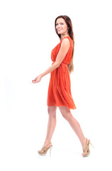 Pretty young female model in dress walking on white and smiling