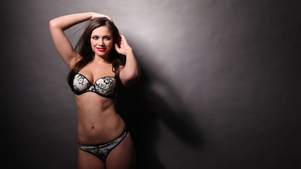 Seductive woman in sexy lingerie over the grey background
