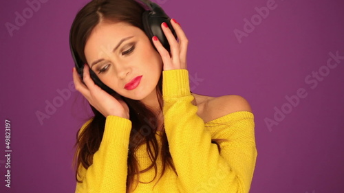 Smiling young woman listening music in headphone