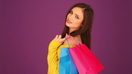 Smiling woman holding shopping bags on her shoulder