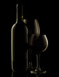 Red wine bottle and glass on dark background