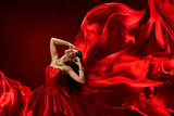Woman in red dress blowing with flying fabric