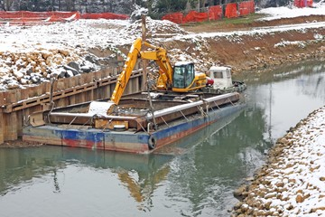 bulldozer Digger in a barge during the work of the River