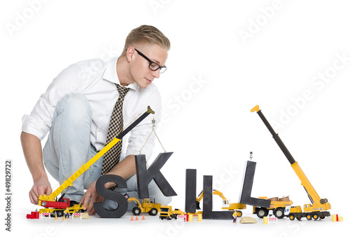 Developing skills: Businessman building skill-word.