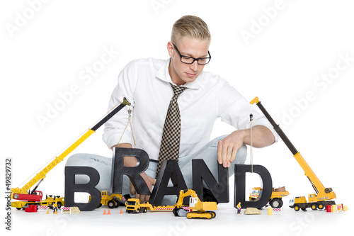 Brand start up: Businessman building brand-word.