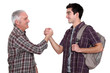 Mature man and young man handshaking